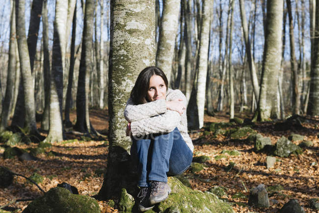 Woman sitting on a rock in a beech forest — Stock Photo