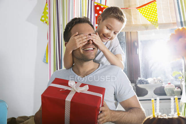 Son Surprising His Father With Birthday Present Stock Photo