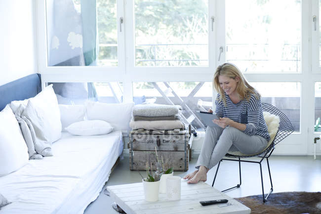 Smiling blond woman using digital tablet at home — Stock Photo