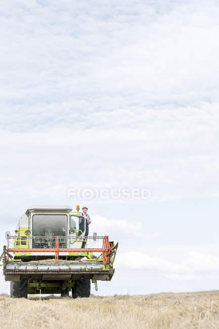 Farmer with combine harvester on field — Stock Photo