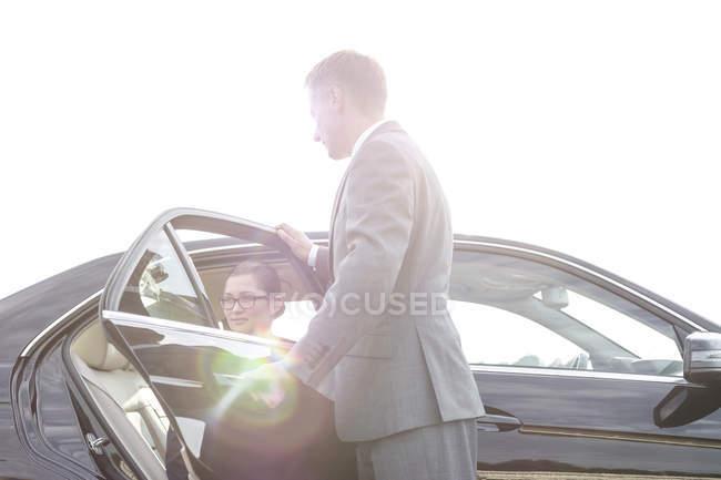 Бізнесмен, відкриваючи двері автомобіля для бізнес-леді вихід — стокове фото