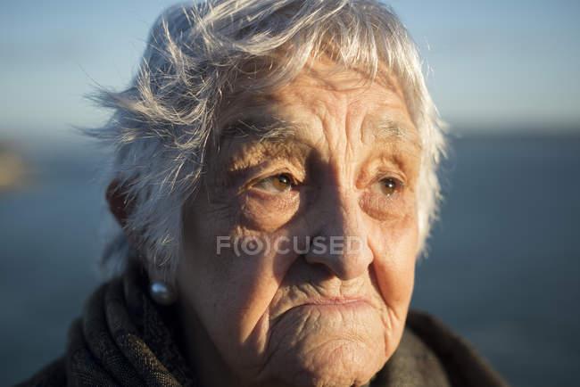 Портрет пожилой женщины, смотрящей на улицу — стоковое фото