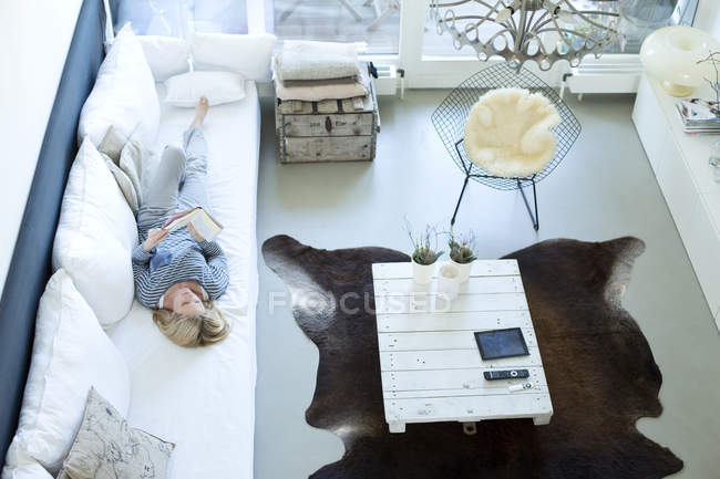 Woman relaxing on couch with a book in her living room — Stock Photo