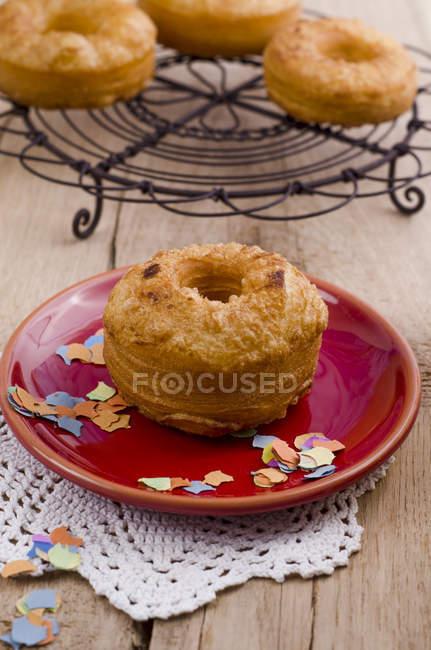 Donut e confetes na placa vermelha no guardanapo — Fotografia de Stock