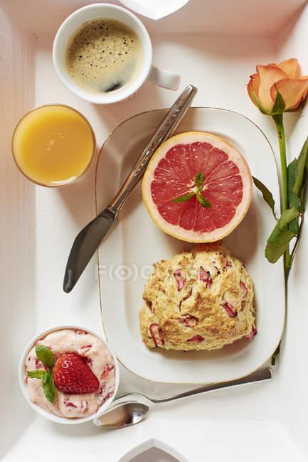 Vassoio con focaccine fatte in casa rabarbaro, burro fragola, pompelmo, succo di frutta fresco e caffè — Foto stock