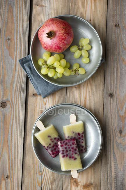 Piatti con selfmade uva melograno ghiaccioli, uva verde e melograno su legno — Foto stock