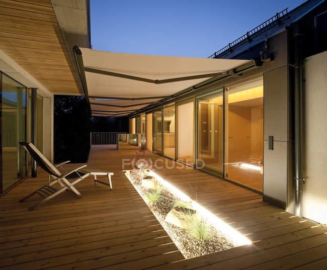Casa unifamiliare, terrazza in legno con tende da sole la sera — Foto stock