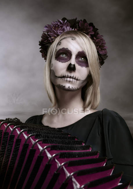 Portrait of woman with sugar skull makeup and accordion — Stock Photo