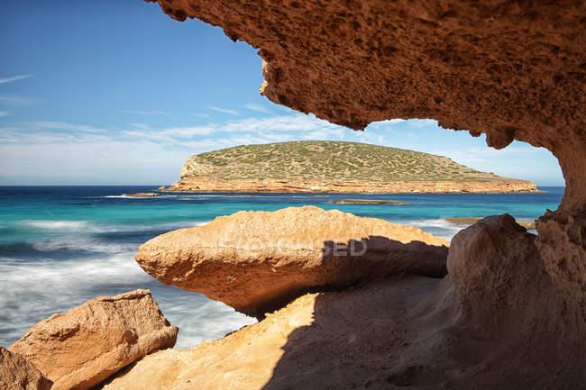 Spagna, Ibiza, Cala Comte, rocce sulla riva contro l'acqua — Foto stock