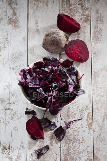 Bowl of leaves and whole and sliced beetroots — Stock Photo