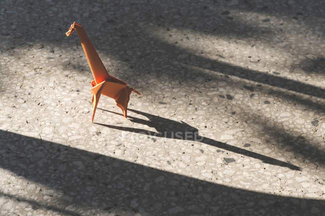 Orange origami giraffe on stone floor — Stock Photo