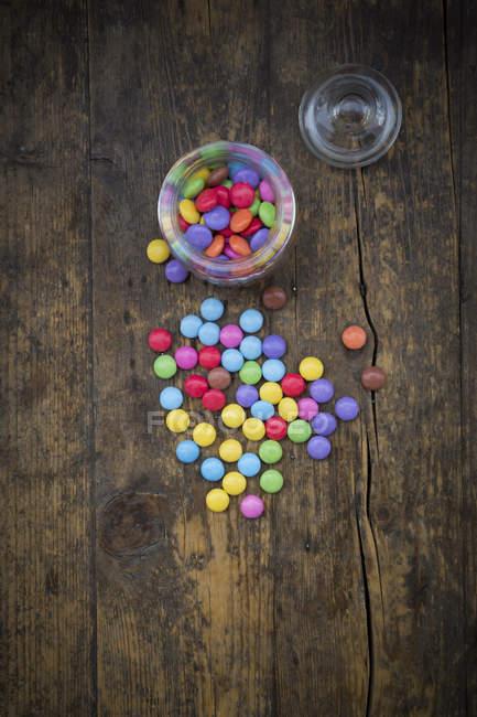 Smarties, pot de bonbons et couvercle en verre sur bois — Photo de stock