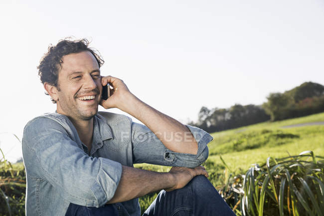 Laughing man sitting on a meadow telephoning with smartphone — Stock Photo