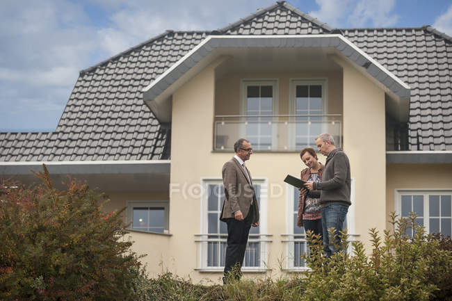 Agente immobiliare con potenziali acquirenti davanti casa residenziale — Foto stock