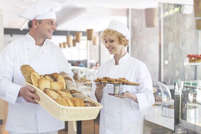 Padeiros com cesta de pão e biscoitos pelo contador na padaria — Fotografia de Stock