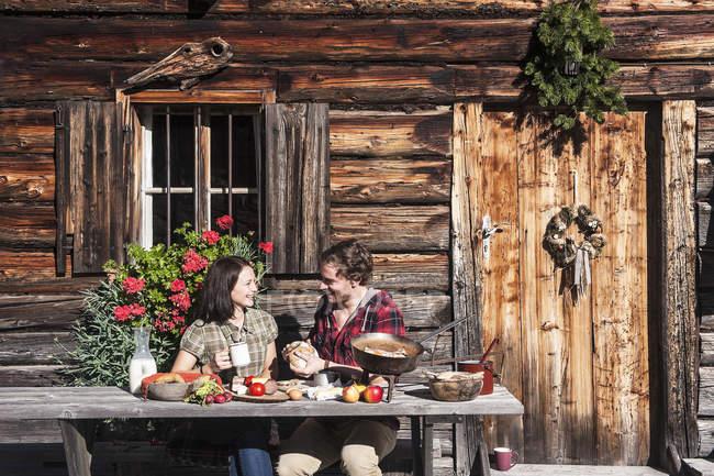 Austria, Altenmarkt-Zauchensee, couple having a break at alpine cabin — Stock Photo