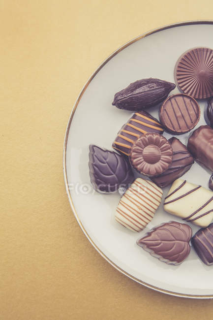 Chocolate candies on plate and yellow background — Stock Photo