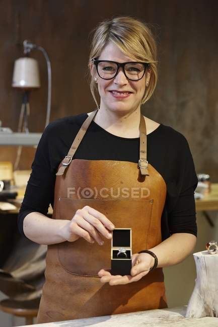 Portrait of smiling goldsmith in her shop presenting jewelry box — Stock Photo