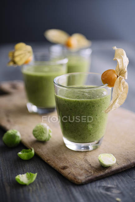 Green smoothie with brussel sprout, banana and apple juice garnished with physalis — Stock Photo