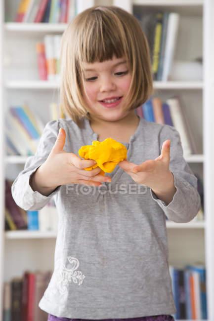 Porträt eines kleinen Mädchens mit gelber Modelliermasse — Stockfoto