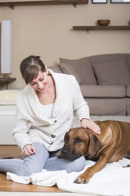 Femme caressant son chien Rhodésien Ridgeback — Photo de stock