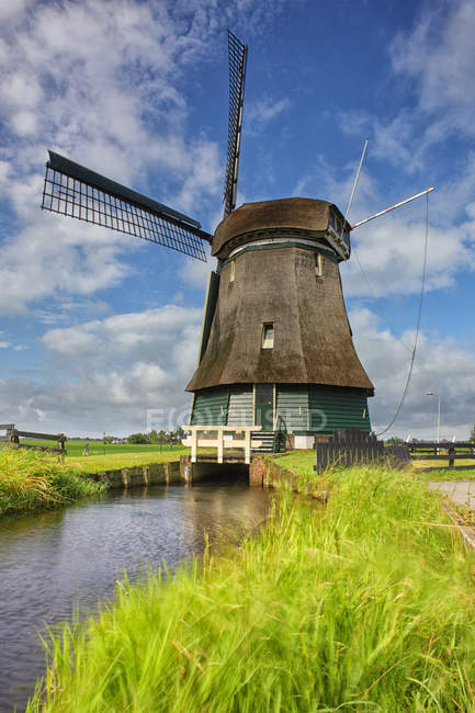 Netherlands, North Holland, Volendam, windmill over water — Stock Photo