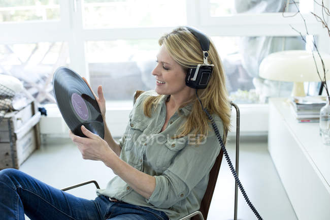 Woman holding record hearing music — Stock Photo