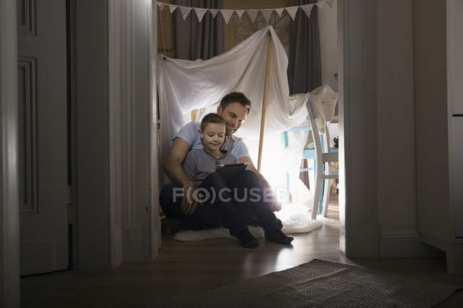Father and son sitting in self-made tent  at home in the evening using digital tablet — Stock Photo