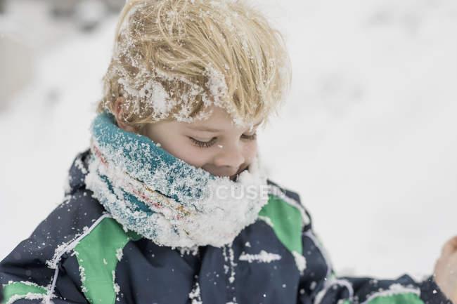 Ragazzo felice che gioca con la neve in inverno — Foto stock