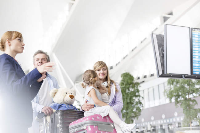 Flight attendant advising family at the airport area — Stock Photo
