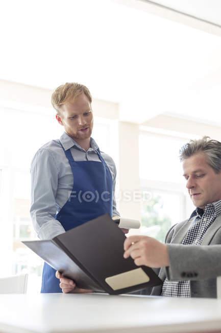 Hombre en el restaurante el pedido - foto de stock