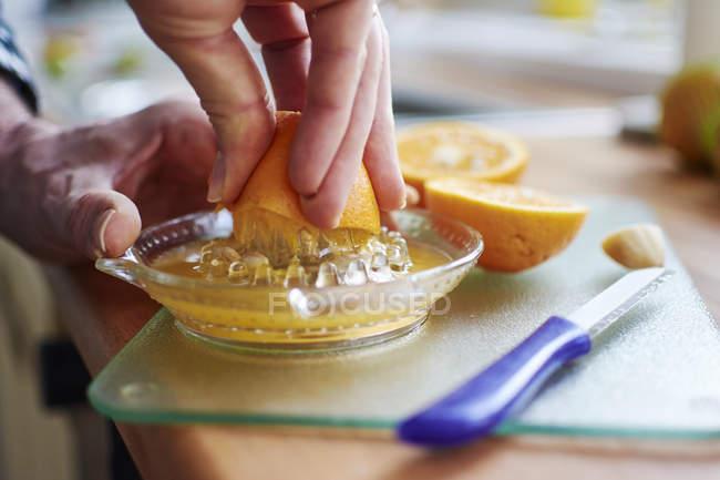 Primer plano de las manos humanas exprimiendo naranjas frescas - foto de stock