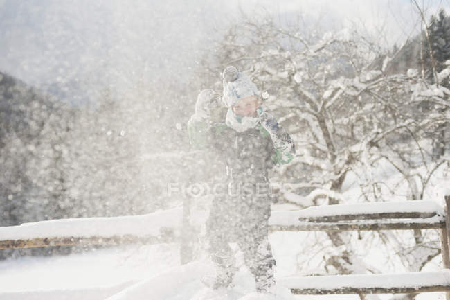 Germany, Bavaria, Berchtesgadener Land, happy boy playing in winter landscape — Stock Photo