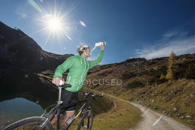 Austria, Altenmarkt-Zauchensee, giovane con rifrazione in mountain bike al lago di montagna — Foto stock