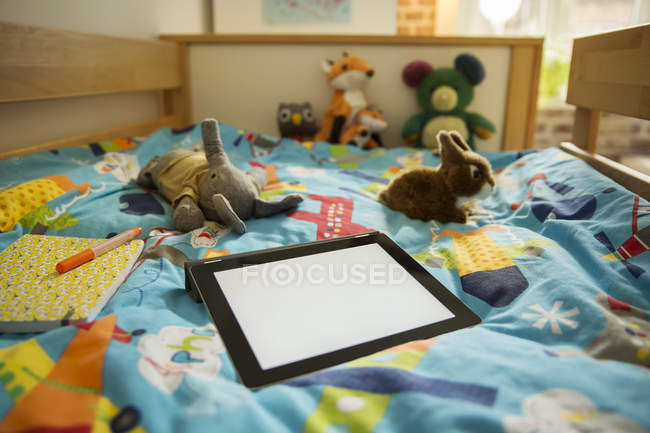 Tablet computer and soft toys on bed in children's room — Stock Photo