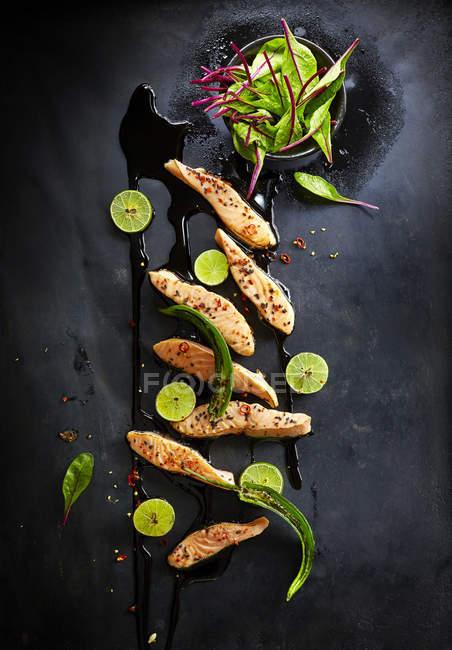 Gebratener Lachs garniert mit Kalk, schwarzem Sesam, Mangold, rote Chili und grüne Chilischote auf schwarze Oberfläche — Stockfoto