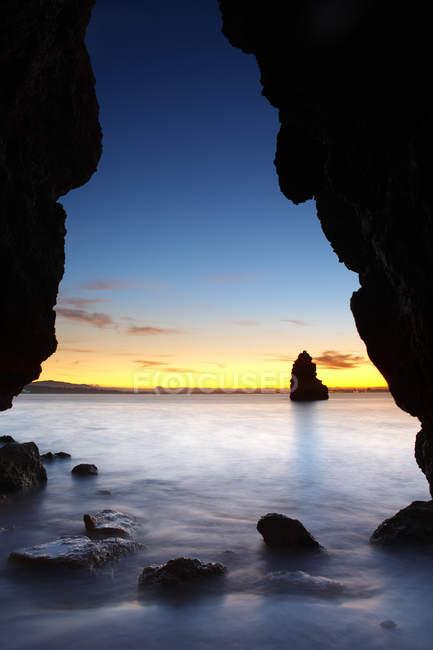 Скельні утворення на березі океану на заході сонця — стокове фото