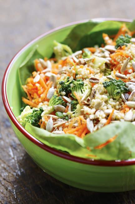 Ensalada de quinua con zanahorias, brócoli, cebolletas, espinacas y semillas de girasol con aderezo de tahini - foto de stock
