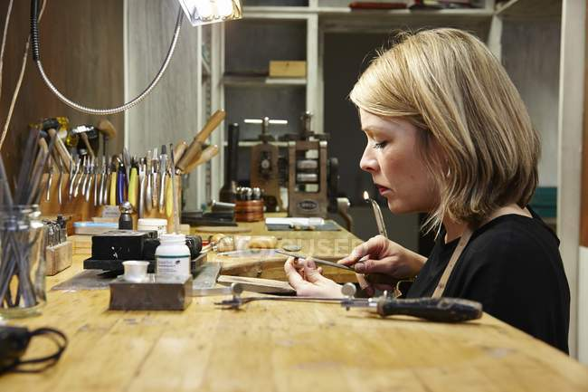 Goldsmith in workshop at work — Stock Photo