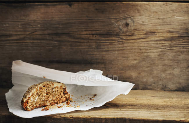 Home-made pastry on paper bag on wooden background — Stock Photo