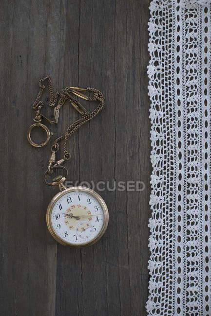 Reloj de bolsillo viejo y encaje en madera oscura - foto de stock