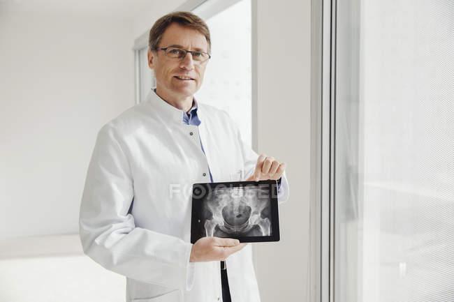 Homem maduro em jaleco apresentando uma varredura de raios X em seu tablet digital — Fotografia de Stock