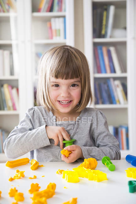 Portrait of smiling little girl playing with yellow modeling clay — Stock Photo
