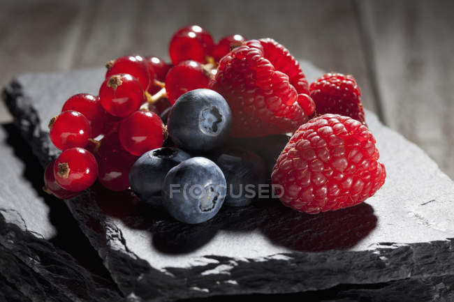 Raspberries with blueberries and red currants — Stock Photo