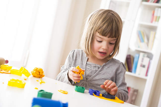 Little girl playing with yellow modeling clay — Stock Photo