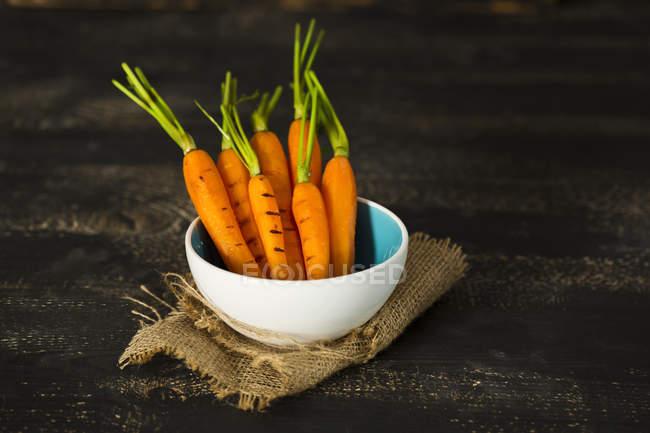 Zanahorias a la parrilla en un tazón de madera oscura con saco - foto de stock