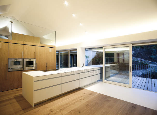 Home ownership, modern open plan kitchen in the evening — Stock Photo