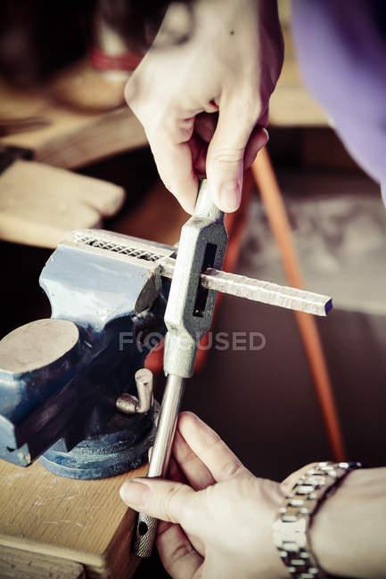 Голдсмит работает над обручальными кольцами в стиле Мокуме Гейна, готовит скамейку порока — стоковое фото