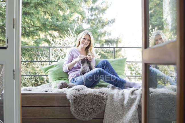 Mulher sentada na varanda tricô — Fotografia de Stock