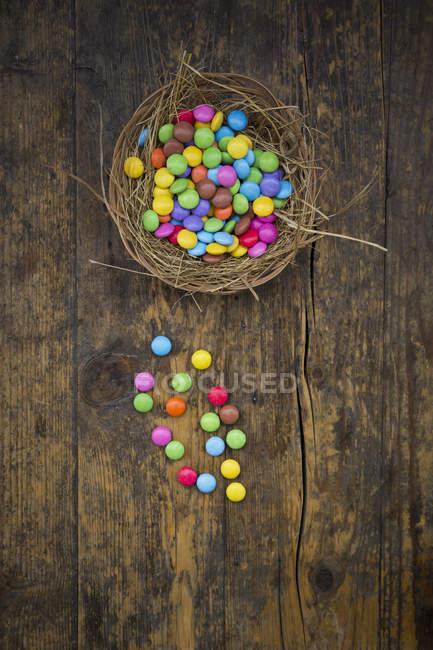 Ninho de Páscoa com doces coloridos, vista superior — Fotografia de Stock